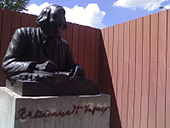Outdoors bronze statue (depicting Tagore at a desk and writing in a book) on a stone plinth with inscribed cursive name.