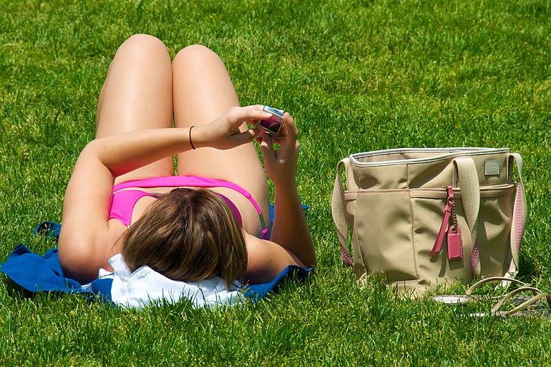 File:Texting while sunbathing.jpg