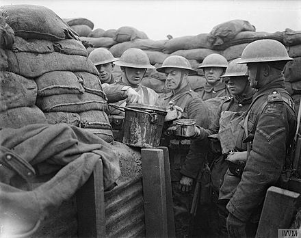 Serving hot stew to the troops of the Lancashire Fusiliers in the front line trench from a container. Opposite Messines, near Ploegsteert Wood, March 1917. The British Army on the Western Front, 1914-1918 Q4843.jpg