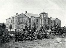 A black and white photograph of a large mansion house, surrounded by various trees