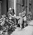 Two girls prepare to carry food scraps to the pig bin at the corner of their road in East Barnet, 1943. D14254.jpg