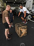U.S. Navy Logistics Specialist 2nd Class Tommy Garland, right, performs a box jump in the hangar bay of the aircraft carrier USS Nimitz (CVN 68) while exercising with Lt. Cmdr. Tim Osborne, left, and Master 130731-N-TX484-056.jpg