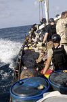 U.S. Navy and Marine Corps visit, board, search and seizure team members stationed aboard the guided missile cruiser USS San Jacinto (CG 56) stand guard over suspected pirates on board a dhow as they travel 100527-N-EF447-029.jpg