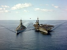 Two large warships sailing toward the viewer. On the left is a gunship, while the right ship is an aircraft carrier. A hose can be seen connecting both ships near the water line, while in the distance a helicopter can be seen in the background.