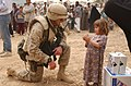 US Navy 030408-N-5362A-007 U.S. Marine Corps Major Chris Hughes shares some time with an Iraqi girl during an effort to distribute food and water to Iraqi citizens in need.jpg
