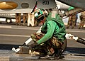 US Navy 040224-N-3986D-027 Aviation Boatswain's Mate Airman Alfred Noce directs the final aircraft positioning of an F-14B Tomcat.jpg