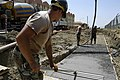 US Navy 040723-N-5821W-015 Seabees assigned to Naval Mobile Construction Battalion Seven Four (NMCB 74), smooth out freshly poured concrete at a construction site aboard the naval station.jpg
