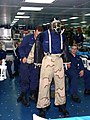 US Navy 040819-N-4207M-003 Damage Controlman 2nd Class Denny Christensen assists Fireman Darnell Lewis don an Advanced Chemical Protective Garment (ACPG).jpg