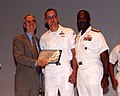 US Navy 041015-N-1648R-001 Secretary of the Navy, the Honorable Gordon R. England and Commander, Naval Forces Marianas, Rear Adm. Arthur J. Johnson, presents Fireman William Swope, center, with his Enlisted Surface Warfare pin.jpg