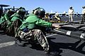 US Navy 041118-N-5384B-033 Crew members aboard the Nimitz-class aircraft carrier USS Abraham Lincoln (CVN 72) use all their strength to hoist the barricade during an emergency-landing barricade drill on the flight deck.jpg
