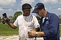 US Navy 050906-N-6436W-402 U.S. Navy Electronics Technician 1st Class Doug Winslow is given a name by an evacuee in an attempt to locate a family member of another Hurricane Katrina victim.jpg
