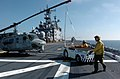 US Navy 051114-N-9866B-055 An Aviation Boatswain's Mate directs the driver of a tow tractor as he backs a U.S. Marine Corps UH-1N Huey helicopter to its parking space.jpg