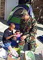 US Navy 051223-N-0000X-001 Construction Mechanic 1st Class Michael Morosko assigned to Naval Mobile Construction Battalion One (NMCB-1) delivers holiday gifts to a 7-year-old military dependant, who is seen taking a gift for hi.jpg
