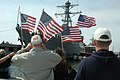 US Navy 060309-N-9562H-015 Family members wave American flags as they anxiously await their loved ones aboard the guided-missile destroyer USS Donald Cook (DDG 75) to pull into port.jpg