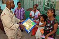 US Navy 071218-N-3931M-019 U.S. Navy Hospital Corpsman 1st Class Ronie Thompson, from Combined Joint Task Force-Horn of Africa (CJTF-HOA), presents a gift to a local resident during a toy distribution project.jpg