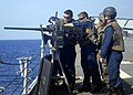 US Navy 090525-N-4879G-491 A Honduran Infanteria De Marine waits as U.S. Navy Sailors clear a jam in a .50 caliber machine gun during a multi-national gunnery exercise aboard the guided-missile frigate USS Doyle (FFG 39).jpg