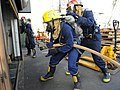US Navy 090914-N-5345W-209 Fire team members begin to make their way into a smoke-filled boat deck space while responding to a simulated fire during a damage control drill aboard the amphibious dock landing ship USS Fort McHenr.jpg