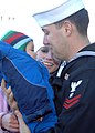 US Navy 101223-N-5292M-180 Hull Maintenance Technician 2nd Class Woren Walken greets his wife and seven-month-old son during a homecoming celebrati.jpg