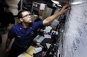 US Navy 120112-N-MD252-101 Aviation Maintenance Administrationman 2nd Class Nicholas Minor, updates a jet engine status board in production control.jpg
