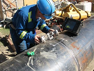 Phased array ultrasonics - At a construction site, a technician tests a pipeline weld for defects using an ultrasonic phased array instrument. The scanner, which consists of a frame with magnetic wheels, holds the probe in contact with the pipe by a spring. The wet area is the ultrasonic couplant that allows the sound to pass into the pipe wall.