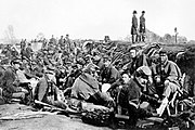 Dozens of soldiers in coats and hats crowd a trench while two others stand tall to the right of the trench.