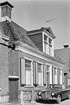 foto van Woonhuis van vijf traveeën breed met omlijste ingang onder schilddak met dakkapel met fronton en hoekschoorstenen waarop borden