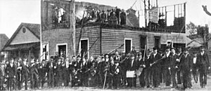 "Wilmington insurrection of 1898 - A photograph showing a group of rioters posing outside the ruins of the ""Record"" building"