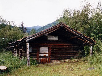 Wiseman, Alaska - The log-built post office at Wiseman, seen here in 1995, has been sinking into the ground for the past century, and is now a couple of feet below ground.