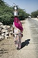 Woman with a pink head scarf carrying water pots, Rajasthan (6361062989).jpg