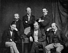A group of six middle-aged men in dark jackets and ties, three seated and three standing