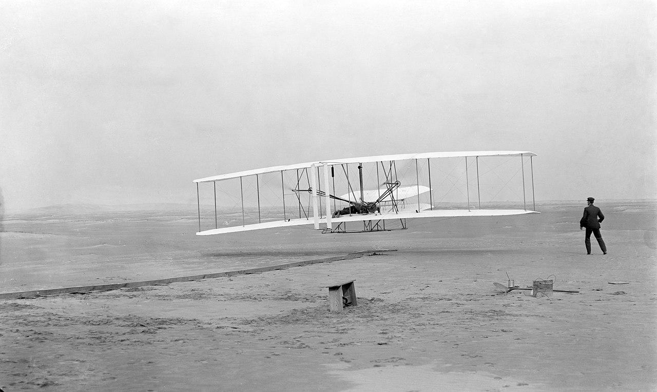 Fotografía original del primer vehículo volador construído por nuestra especie.  En la fotografía aparecen Orville Wright (a bordo de la bicicleta con alas) y Wilbur Wright (a la derecha).  Fotografía de la biblioteca del Congreso de los Estados Unidos (Wikimedia).