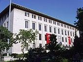Un bâtiment blanc à toit plat de quatre étages avec deux drapeaux turcs et un portrait à l'extérieur