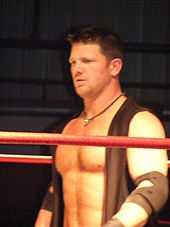 An adult white male wearing a black vest standing in a wrestling ring with red ropes.