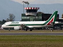 Un A320 Alitalia e sullo sfondo la torre di controllo gestita da ENAV.