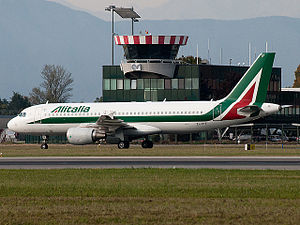 Turin Airport - An Alitalia Airbus A320-200 taxiing at Turin Airport in front of the control tower