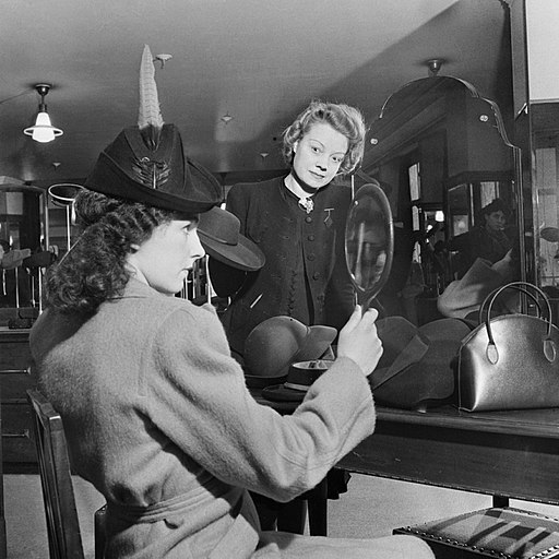 A customer tries on a new hat in the millinery department of Bourne and Hollingsworth on London's Oxford Street in 1942. D6596