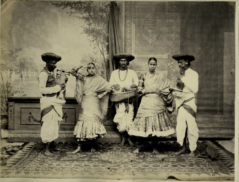 A photograph of two dancing girls and three musicians performing together
