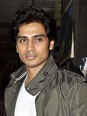 Shiv Panditt in a white T-shirt and camo jacket, looking away from the camera.