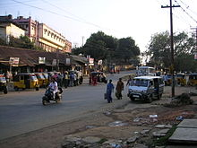 a street in Agartala, showing pedestrians, and many vehicles such as auto-rickshaws, a scooter, and a van