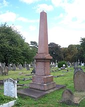 A tall red four-sided obelisk, surrounded by much shorter gravestones