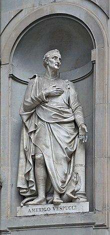 Photographie d'une statue plein pied d'un homme assez âgé la main droite sur la poitrine. À ses pieds se trouve une sorte d'iguane.