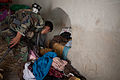 An Afghan soldier sorts through a pile of clothes inside a room while performing a cordon and search operation with U.S. Marines at Sangin, Afghanistan, June 1, 2011 110601-M-QZ858-064.jpg