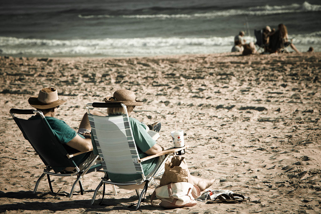 An elderly couple sits on a beach.