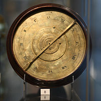 A brass, clock-like mechanical device in a museum display case, with a small card with the number 8 printed on it.  The face of the device is split into several rings, with the Roman numerals I through XI (and 0) on one of these rings.