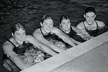 A black-and-white photograph of four girls in a swimming pool all looking at the viewer and smiling while holding onto the side of the pool