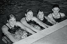 Una fotografia in bianco e nero di quattro ragazze in una piscina che guardano lo spettatore e sorridono mentre si tengono sul bordo della piscina