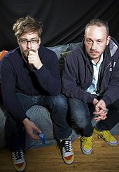 Colour photograph of Felix Buxton and Simon Ratcliffe of Basement Jaxx sitting on a sofa.