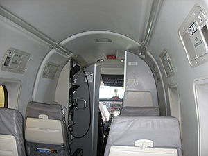 Continental Connection - Facing forward in the passenger cabin of a CommutAir Beechcraft 1900D displaying the integral and remote field operationally friendly, airstair built into the forward exit of this type of airplane