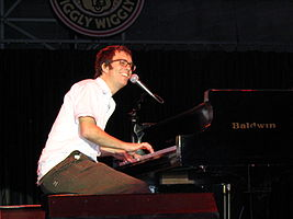 Ben Folds is playing the grand piano and smiling in this photograph which was taken June 25, 2004