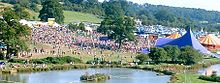 An aerial shot of a large gathering of people in a grassy area beside a lake. Several large tents are visible.